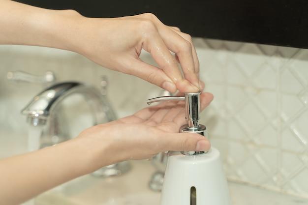 La mano della donna usa il sapone e lava sotto il rubinetto dell'acqua. concetto di igiene.
