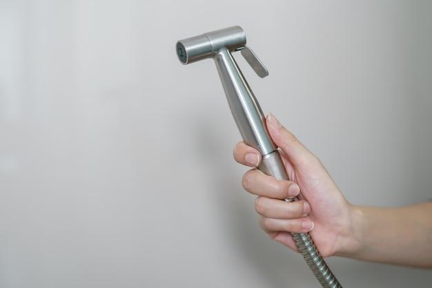 Mano della donna facendo uso della doccia del bidet del cromo che si siede sulla toilette.