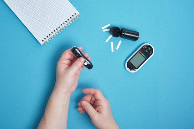 Mano della donna che utilizza una lancetta sul dito per controllare lo zucchero nel sangue utilizzando un glucometro, diabete, glicemia, concetto di assistenza sanitaria. sfondo blu copia spazio vista dall'alto