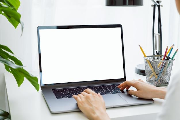 La mano della donna che per mezzo del computer portatile sulla tavola in casa, deride su dello schermo in bianco.