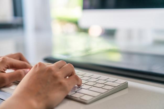 Mano della donna che per mezzo del computer portatile per lavorare studio sullo scrittorio del lavoro con il fondo pulito del fondo della natura. business e finanziario, stock stock e social network.