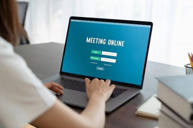 Mano della donna facendo uso del login al sito web della riunione online sul computer portatile a casa. concetto di lavoro da casa.