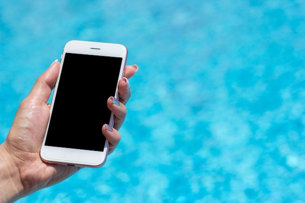 Mano della donna facendo uso dello smartphone vicino alla piscina, primo piano