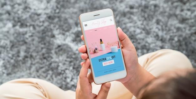 Mano della donna che utilizza l'applicazione dello schermo dello smartphone di cosmetici online. bottiglia di siero, mockup del marchio di prodotti di bellezza.