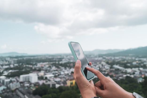 Mano della donna che utilizza smartphone per fare affari di lavoro, social network, comunicazione con vista sulla città.