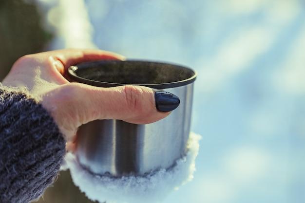 Mano di donna con smalto nero che tiene una tazza di metallo con bevanda calda vacanze invernali in campeggio