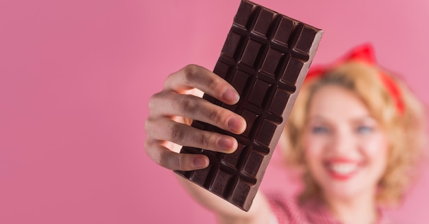 Mano della donna con la barretta di cioccolato. cibo dolce. copia spazio per la pubblicità. messa a fuoco selettiva.