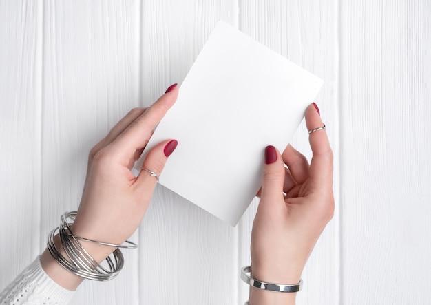 Mano della donna con il minimo rosa primavera estate manicure design tenendo la cartolina d'auguri