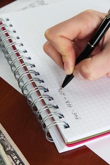 Mano della donna con la penna sul tavolo da lavoro