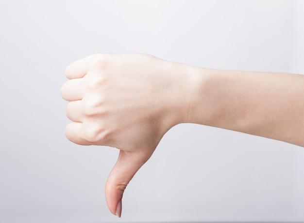 Mano della donna con il pollice verso il basso su uno sfondo bianco