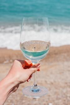 Mano di donna con bicchiere di vino bianco su onde di schiuma di mare mediterraneo turchese e sfondo di spiaggia