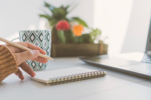 La mano della donna annota in taccuino bianco per prendere una nota da non dimenticare, per fare la lista o pianificare il lavoro in futuro sul tavolo di lavoro.