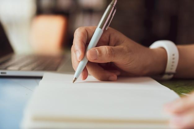 Mano della donna che scrive in piccolo taccuino di appunto bianco per prendere una nota per non dimenticare o per fare il piano dell'elenco per il futuro.