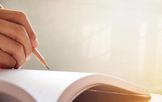 Scrittura della mano della donna sul taccuino