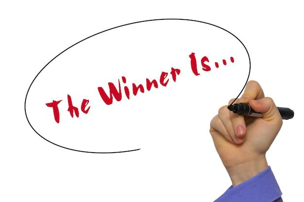 Donna mano scrittura the winner is... a bordo trasparente in bianco con un pennarello isolato su sfondo bianco. concetto di affari. archivio fotografico