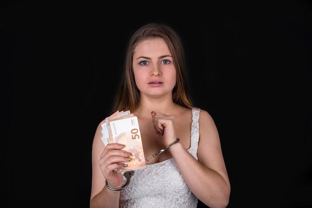 Donna in manette con banconote in euro isolate sul nero