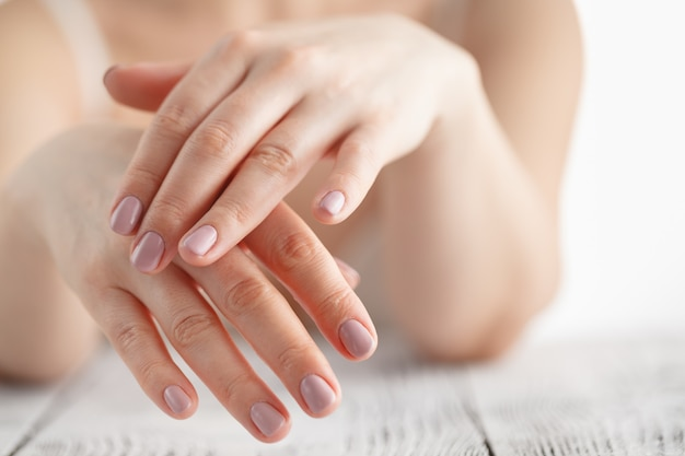 Mani della donna che applicano crema idratante sulla sua pelle