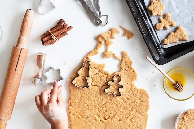 Mani della donna che cuociono i biscotti in cucina