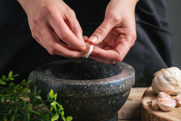 Mani della donna che cucinano mettendo l'aglio nel mortaio