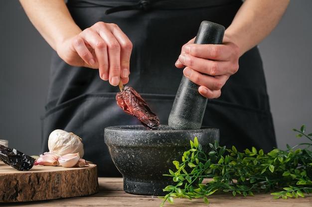 Mani della donna che cucinano mettendo il pepe nel mortaio