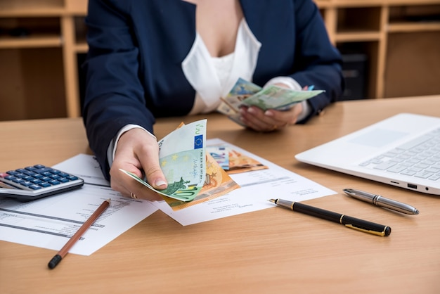 Le mani della donna che contano i soldi dell'euro con la penna e la calcolatrice del laptop del preventivo domestico del documento