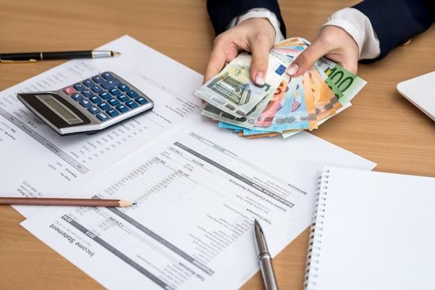 Mani della donna che contano i soldi dell'euro con la penna e la calcolatrice del lapptop del bilancio domestico del documento