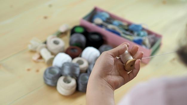 Mani di donna e lavoro artigianale ricamo cucito a mano lavoro artigianale con filo ago cucire maglia