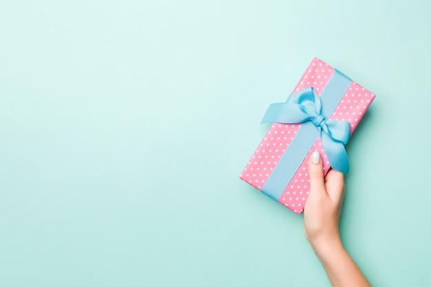 Le mani della donna danno il regalo avvolto del natale o dell'altra festa fatta a mano in carta colorata. scatola attuale, decorazione del regalo sulla tavola blu, vista superiore con lo spazio della copia