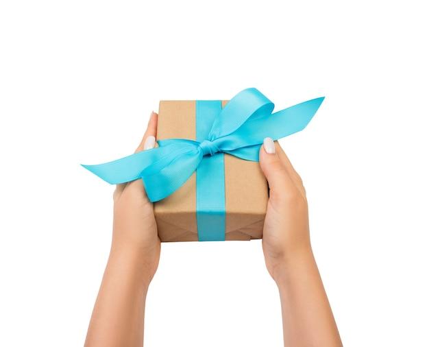 Le mani della donna danno il regalo di san valentino avvolto o altro regalo fatto a mano di festa in carta con il nastro blu. casella attuale, decorazione del regalo isolata su bianco.