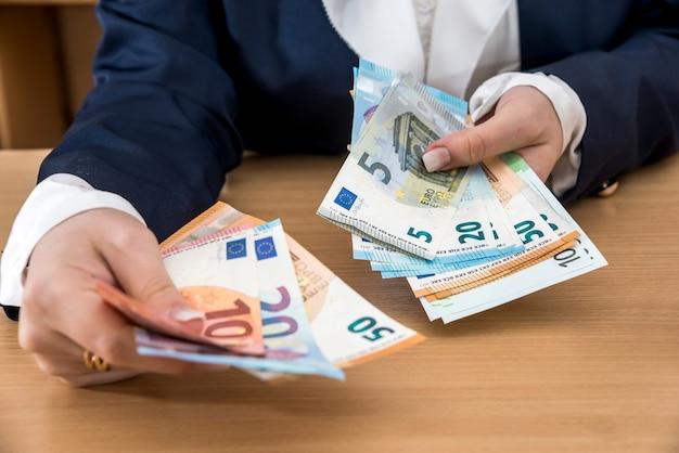 Mani della donna che danno le banconote in euro