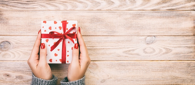 Mani della donna che danno il contenitore di regalo di feste sulla tavola di legno, scatola attuale, decorazione rossa del cuore del regalo sulla tavola di legno, vista superiore con lo spazio della copia per voi progettazione. banner web tonico