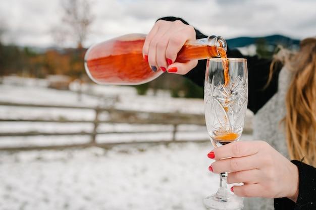 Le mani della donna tengono una bottiglia di champagne e si versa in un bicchiere sulle montagne invernali.