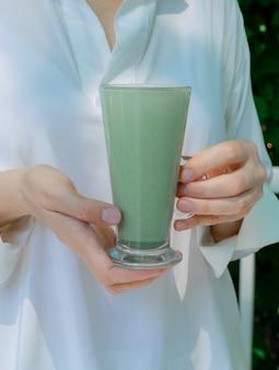 Le mani della donna tengono le foglie verdi di vetro di vetro del tè del caffè del latte del matcha della tazza