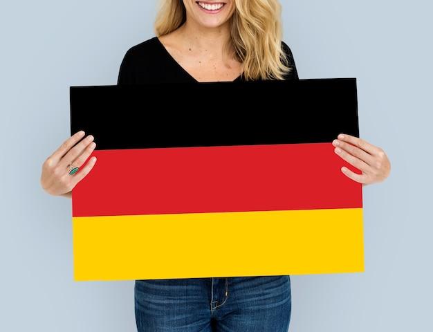 Le mani della donna tengono la bandiera della germania deutschland patriottismo