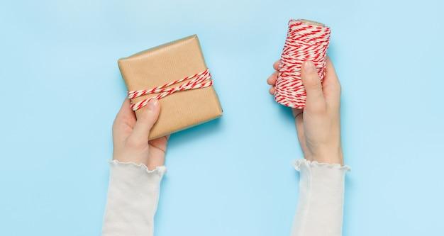 Le mani della donna tengono una confezione regalo e un nastro di spago rosso e bianco