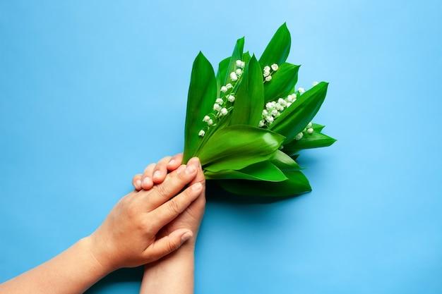Le mani della donna tengono un bouquet di mughetto sullo sfondo blu isolato estate o festa della mamma...