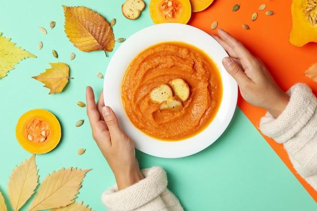 Le mani della donna tengono il piatto di zuppa di zucca su due toni