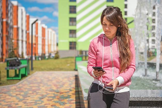 La donna passa la tenuta dello smartphone nero che carica la batteria dalla banca di potere esterna