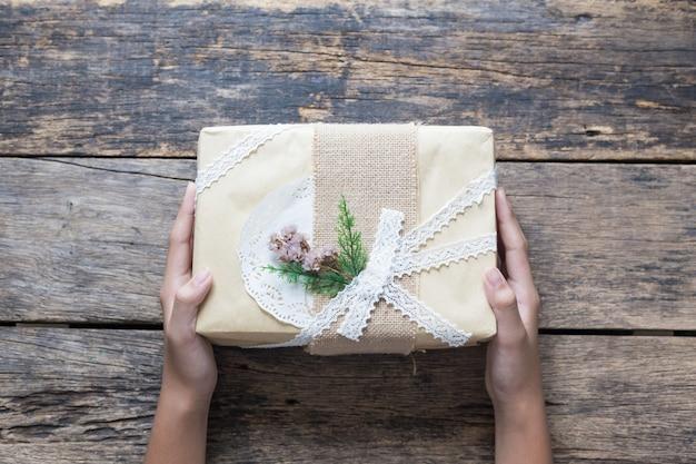 La donna passa in possesso di un regalo di natale sulla vecchia vista dall'alto del tavolo in legno