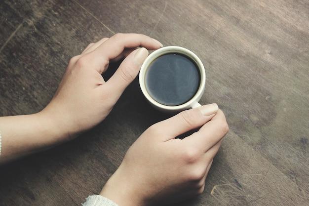 Mani della donna che tengono il caffè sulla tavola di legno