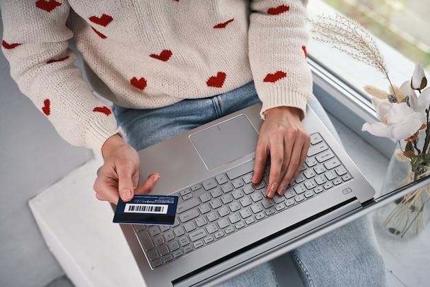 Mani di donna che tengono la carta di credito e utilizzano il computer portatile per l'acquisto in internet per lo shopping online