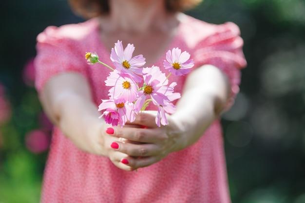 La donna passa la tenuta del fiore in prato verde
