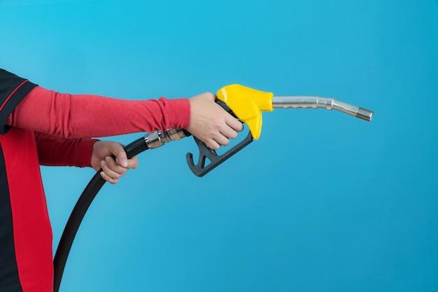 Mani della donna che tengono l'ugello del carburante isolato su priorità bassa blu