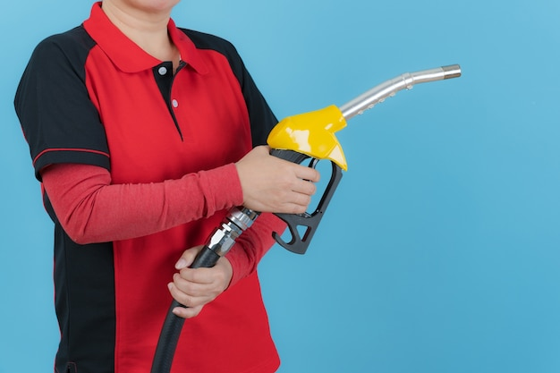 Mani della donna che tengono l'ugello del carburante isolato sulla parete blu