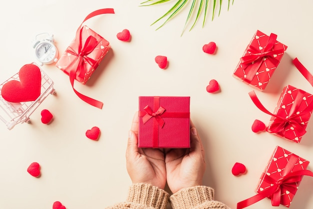 Mani della donna che tengono regalo o presente scatola decorata e sorpresa di cuore rosso su pastello