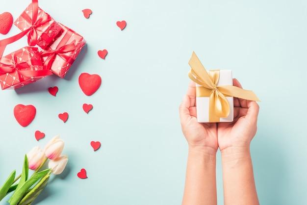 La donna passa il regalo o la presente scatola decorata e sorpresa del cuore rosso