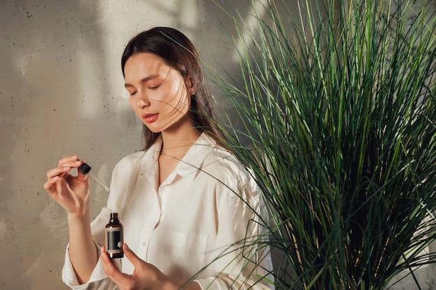 Mani della donna che tengono la bottiglia di olio per massaggi o cosmetici per l'applicazione di gocce sulla pelle del viso. olio femminile della stretta sul vecchio fondo della parete con ombra dal fogliame. concetto di stile di vita sano e cura di sé