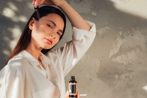 Mani di donna che tengono una bottiglia di olio per massaggi o cosmetici per applicare gocce sulla pelle del viso. olio femminile della stretta sul vecchio fondo della parete con ombra dal fogliame. concetto di stile di vita sano e cura di sé