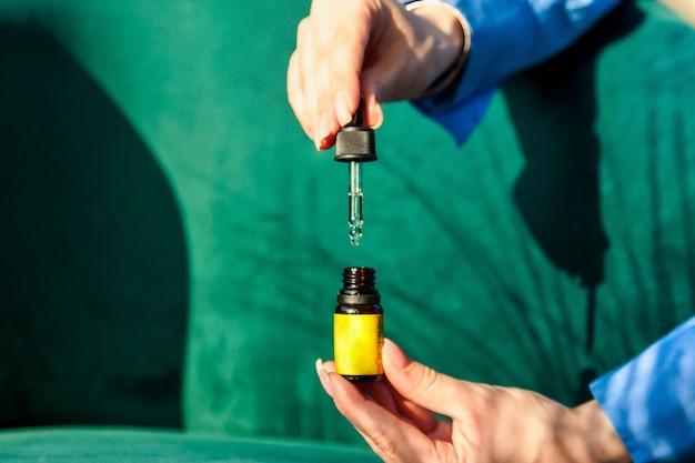 Mani della donna che tengono la bottiglia di olio dei cosmetici o di massaggio. olio essenziale di primo piano nelle mani. vista ad alto angolo della bottiglia di olio da massaggio su sfondo vecchio. concetto di stile di vita sano e cura di sé. copia spazio