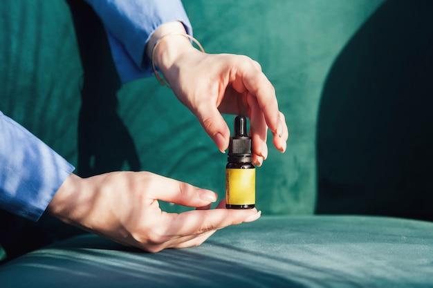 Mani della donna che tengono le bottiglie di olio dei cosmetici o di massaggio. chiudere l'olio essenziale sulla sedia. vista ad alto angolo della bottiglia di olio da massaggio su sfondo verde. concetto di stile di vita sano e cura di sé. copia spazio